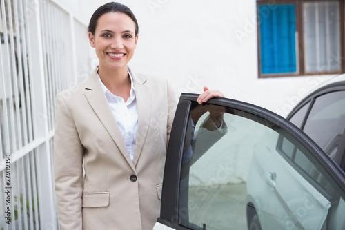 Leinwanddruck Bild Smiling businesswoman standing beside her car