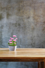 plastic flowers with pot on table in front of wall