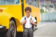 Cute pupil smiling at camera by the school bus - 77990183
