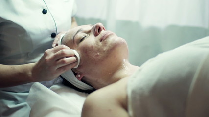 Cosmetician cleaning woman's face with cotton pads