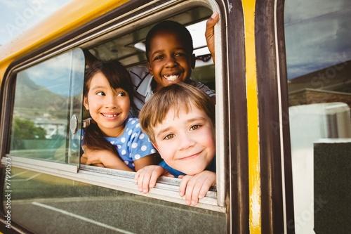 Leinwanddruck Bild Cute pupils smiling at camera in the school bus