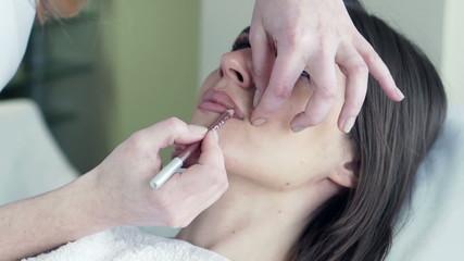 beautiful woman getting permanent lips makeup at beauty salon
