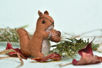 Handmade squirrel toy eating nuts into the forest
