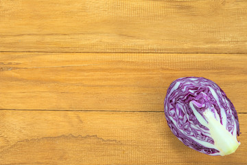 Quarter section of purple round cabbage over wooden background