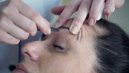 Woman getting tweezing her eyebrows by beautician
