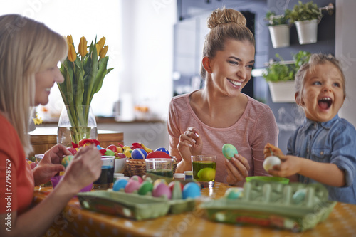 Painting eggs with family before Easter - 77998929