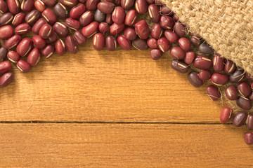 Azuki bean pour out of grunge sack on top of orange wooden table