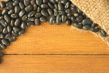 Black bean pour out of grunge sack on top of orange wooden table