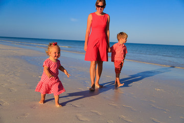 mother and two kids walking on beach
