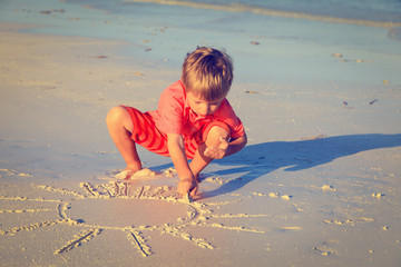little boy drawing sun on sand beach