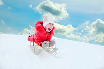 happy, cheerful, screaming child in red clothes rides the hills