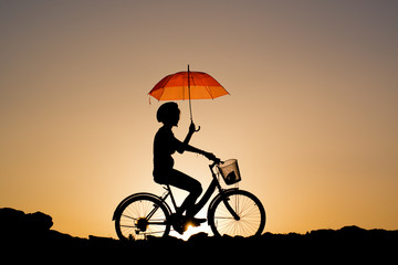 Silhouette of Young girl riding a bicycle holding a red umbrell