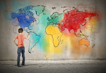 Young boy drawing a world map