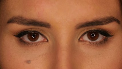 Beautiful brown eyes of young brunette woman, close up