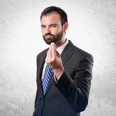 Young businessman doing a money gesture over white background