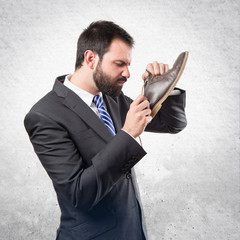 Young businessmen smelling his shoes over isolated background.