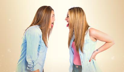 Girls doing a joke over isolated white background
