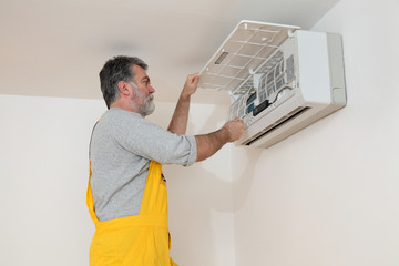 Electrician worker examine,cleaning air condition in room