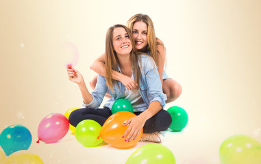 Friends with many balloons over white background