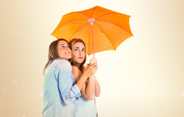 Friends holding an umbrella over white background