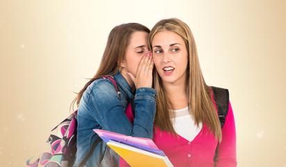 Student women whispering over white background