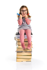 Surprised little girl with glasses sitting on books