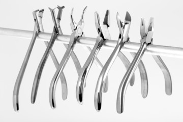 A set of six orthodontic pliers on a white background