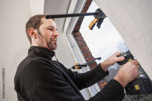 Carpenter mounting a new window - 78008533
