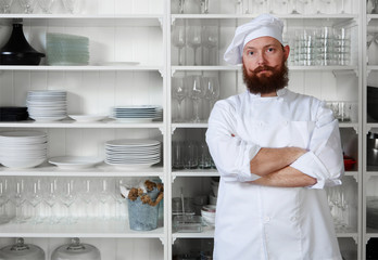 Confident and experienced chef cook standing on kitchen