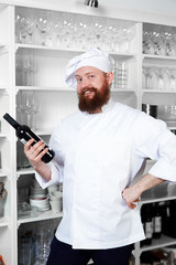 Smiling chef cook holding bottle of red wine in the kitchen