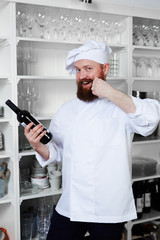 Chef hold exclusive bottle of champagne rubbing mustache