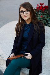 Young elegant woman using a digital tablet sitting outdoors