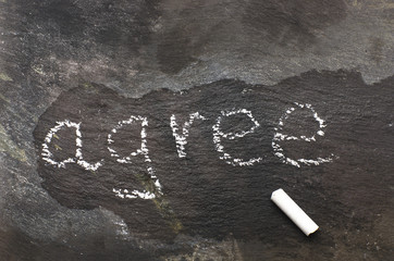 The word agree written with chalk on black stone.