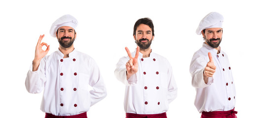 Chef doing victory gesture over white background
