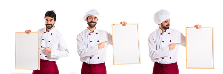 Handsome chef holding empty placard
