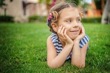 little girl in striped vest lies on green lawn
