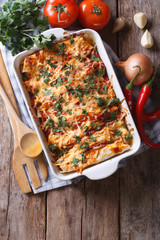 Mexican enchilada in a baking dish vertical top view