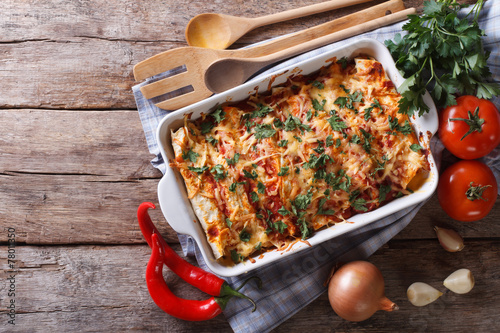 Mexican enchilada in a baking dish horizontal top view - 78011350