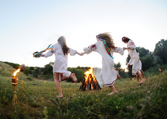 Girls in Ukrainian national shirts dancing around a campfire