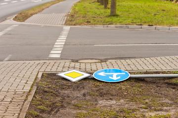 Ein Pfahl mit Verkehrsschildern liegt umgekippt am Strassenrand