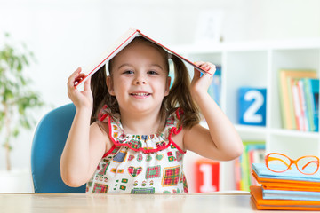 Student child with a book over her head