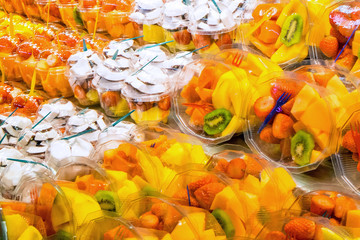 Many different fruit salads for sale at a market