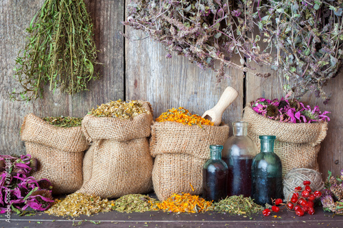 Leinwanddruck Bild Healing herbs in hessian bags and bottles of essential oil near