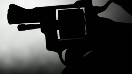 Silhouette of a mans hand with a handgun,real time
