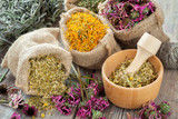 Healing herbs in hessian bags, wooden mortar with chamomile on r