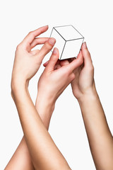 Hands holding white cube