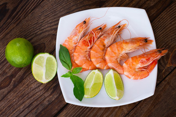 Delicious fresh seafood shrimp with lime on wooden table