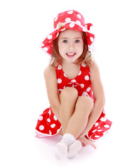 beautiful little girl in a red polka-dot dress sitting on the fl