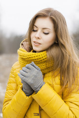 Pretty woman in a yellow knit scarf. Warm hands. Looking down.