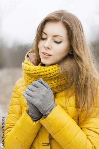 canvas print picture Pretty woman in a yellow knit scarf. Warm hands. Looking down.
